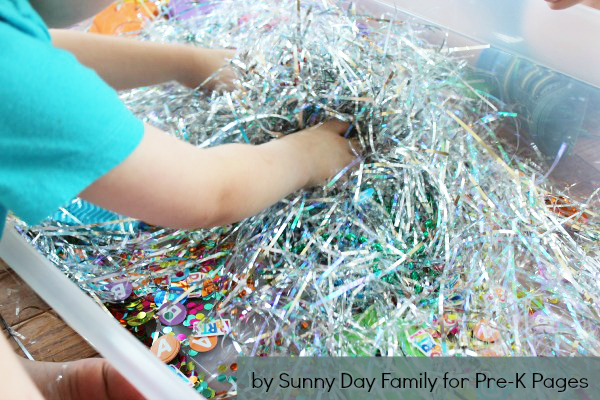 child playing in alphabet sensory bin
