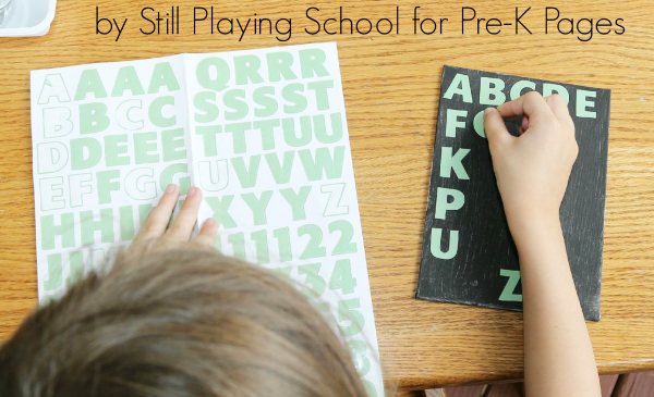 child sticking alphabet stickers on to project
