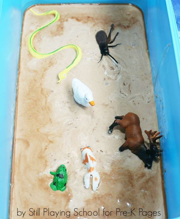toy animals in muck bin for sensory play