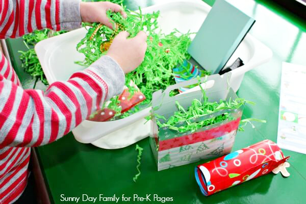 child playing in gift wrap sensory bin