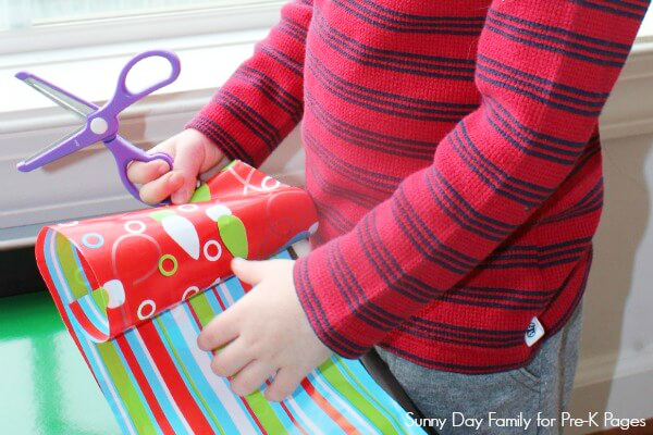 child cutting wrapping paper with scissors
