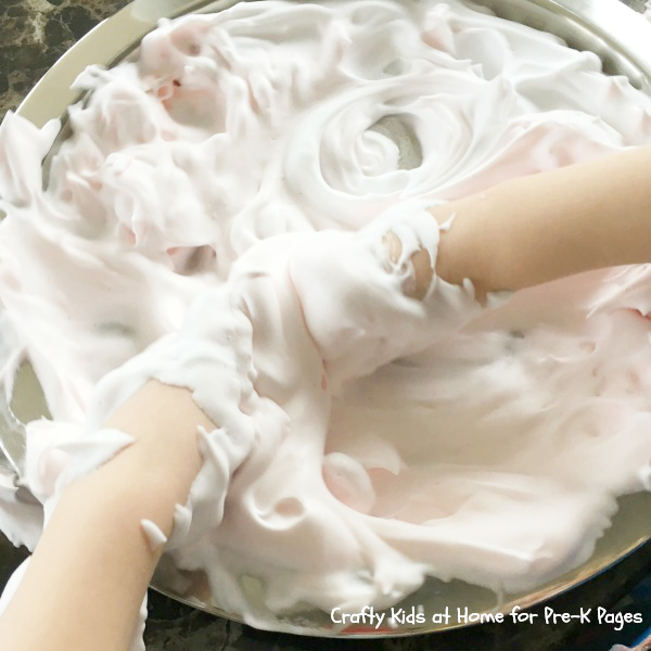hands engaging in sensory play by playing in shaving foam