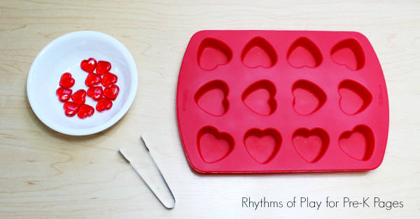 bowl of plastic hearts, tweezers, and a red heart shaped silicone mold