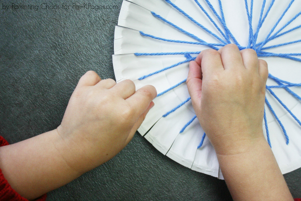 child weaving yarn through paper plate