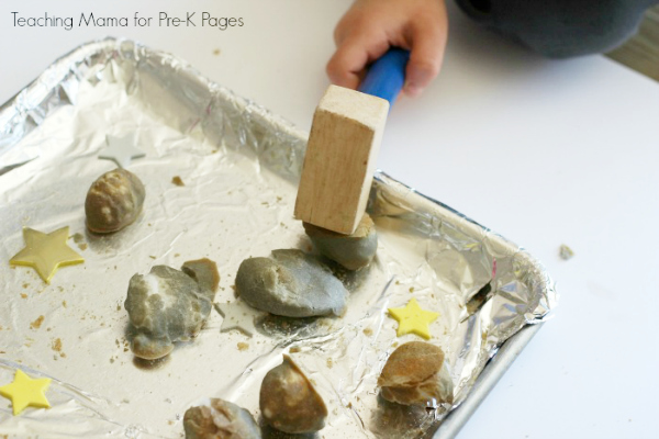 child smashing moon rocks with a mallet