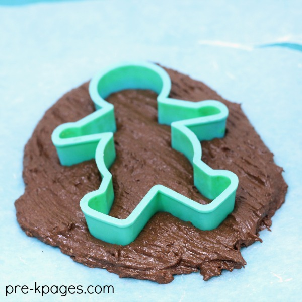 gingerbread cookie cutter placed into dough