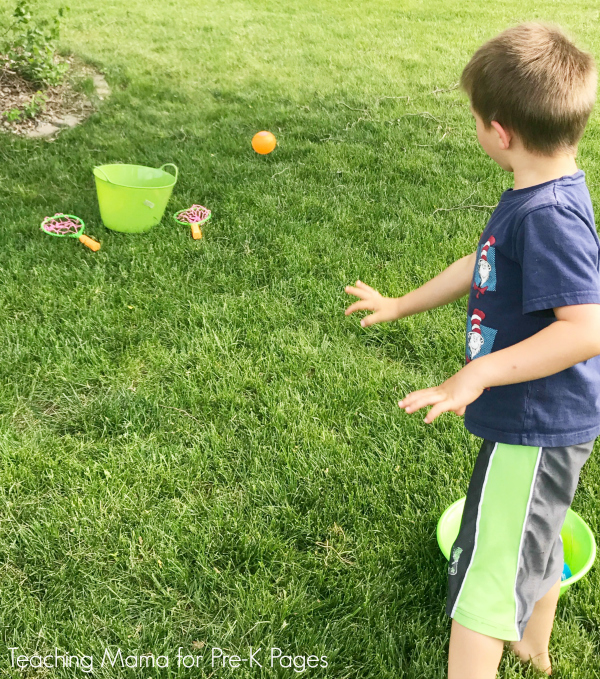 kid throwing ball into bucket for obstacle course for kids