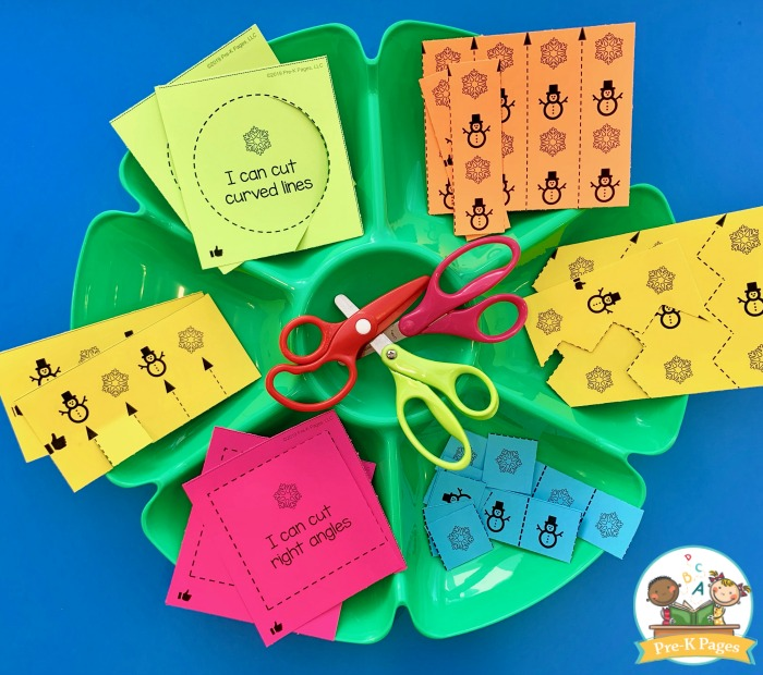 winter scissor skills activity in green tray with scissors